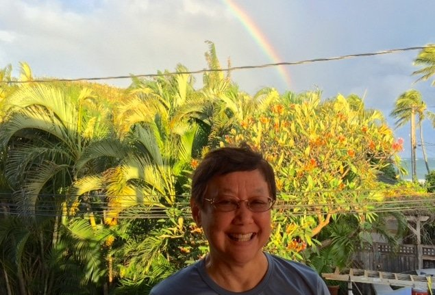 Vanee Songsiridej with rainbow and palm trees in background. Mindfulness, Health, and Community