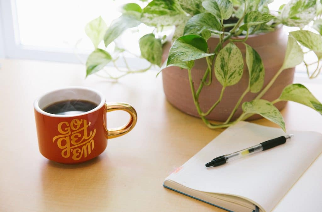 5 tips to improve your newsletter. Picture of plant, coffee, notebook and pen.