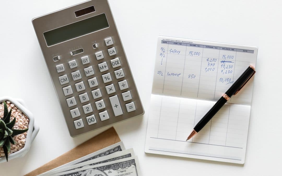 Tax tips for wellness professional. A calculator, ledger and pen.